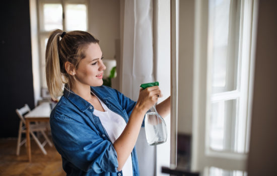 A young woman standing indoors at home, cleaning windows.